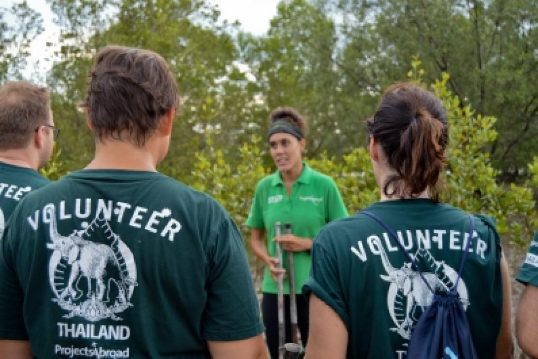 A Conservation project staff member explains mangrove reforestation to volunteers in Thailand